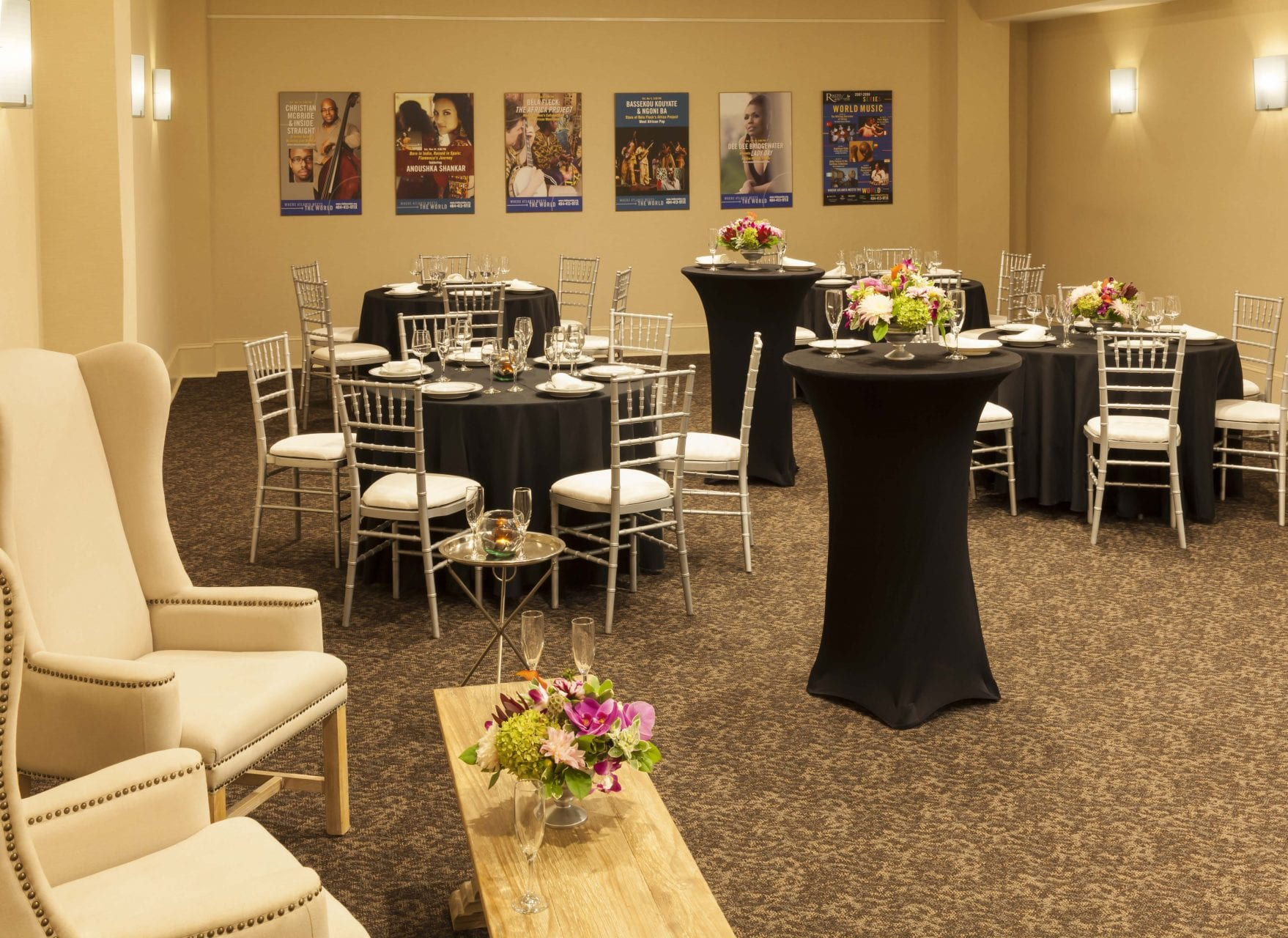 Suite set up for reception with round tables and chairs and seating are with two wing chairs and a coffee table on side